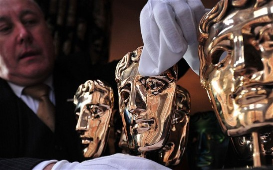 Ein Butler poliert die begehrten BAFTA  British Academy Film Awards in Maskenform, welche als Preise vergeben werden.Photo: AFP/GETTY