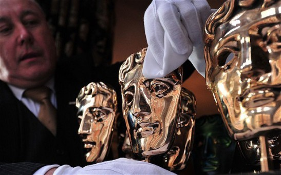 A butler polishes the mask shaped trophies handed out at the BAFTA Photo AFP/ GETTY images